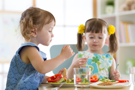 children eating food in daycare centre Stock Photo