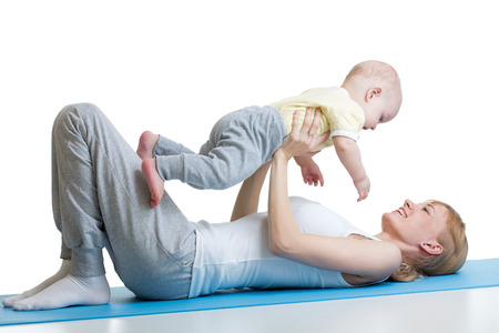 young mother does fitness exercises together with baby boy isolated