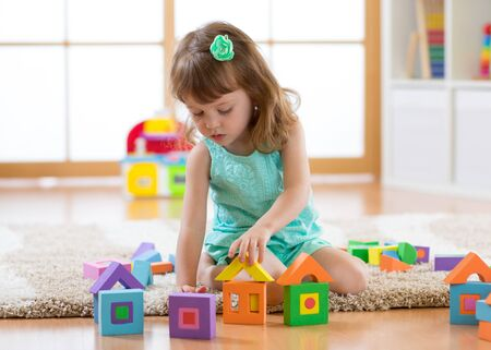 Child girl playing with constructor sitting on the floor