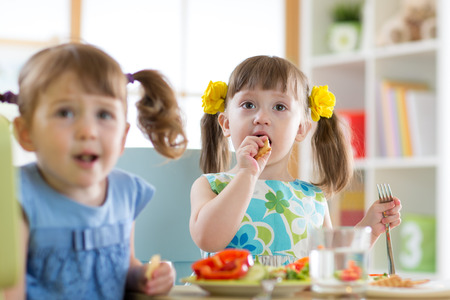 Children eating healthy food and cookie at kindergarten