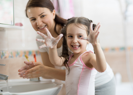 Pretty woman and daughter child girl washing hands with soap in bathroom 스톡 콘텐츠