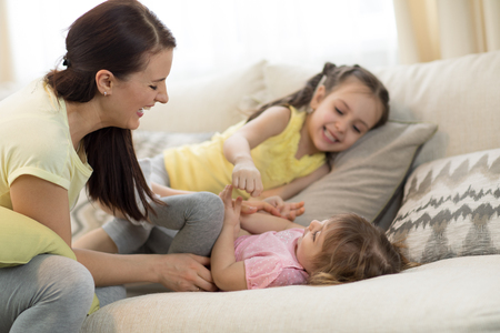 Smiling kids and mom having a fun pastime on sofa in living room at home Banque d'images