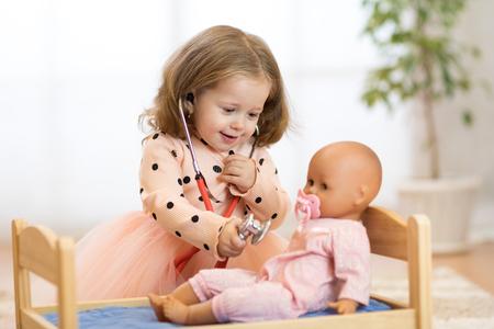 Child in kindergarten. Kid in nursery school. Little girl preschooler playing doctor with doll.