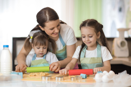 Two little girls and their beautiful mom in aprons are playing and laughing while rolling the dough in the kitchen