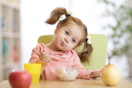 Cute little girl with healthy breakfast at table in kitchen Banque d'images