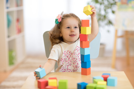 Child stacks building cubes sitting at table in nursery