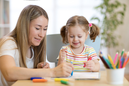 Kindergarten teacher and child girl drawing lessons at school