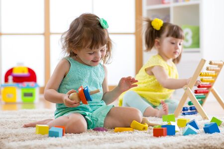 Kids are engaging in daycare. Two toddler children playing with educational toys in kindergarten.