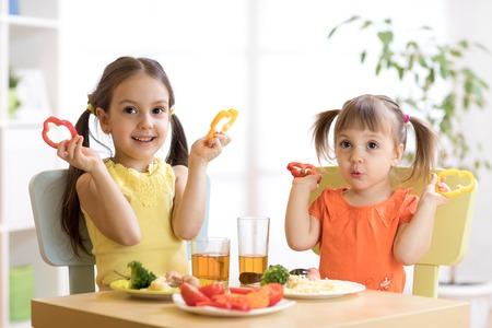 happy kids eating healthy food in kindergarten or at home