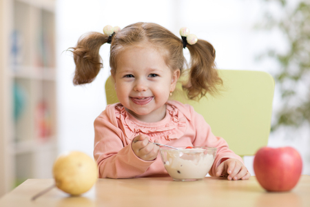 child eating healthy food at home or kindergarten Stock Photo