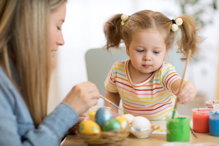 Mother and baby painting on Easter eggs Foto de archivo