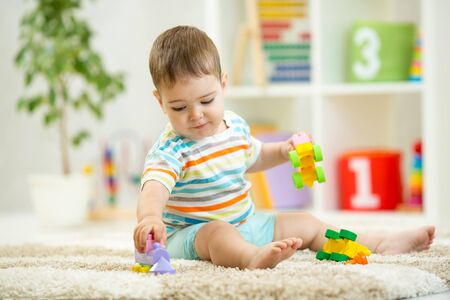 Happy baby playing with colorful plastic bricks on the floor. Toddler having fun and building a train out of constructor bricks. Early learning. Developing toys Stock Photo