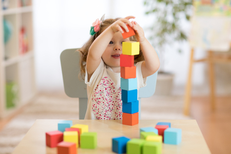 Kid girl playing with block toys in day care center
