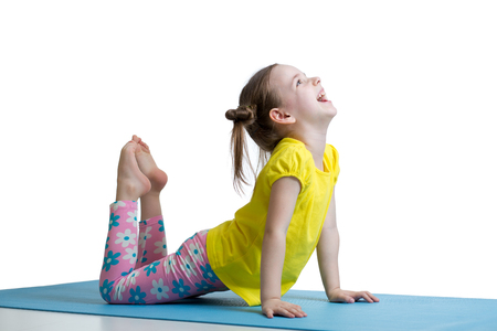 Child doing fitness exercises on mat 스톡 콘텐츠