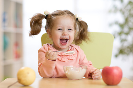 Cheerful baby child eating food itself with a spoon Stock fotó - 96521237