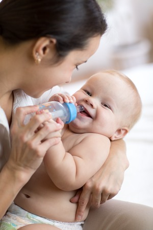 Mother gives to drink water baby from bottle
