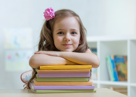 Happy kid girl with a stack of books at home Stock Photo