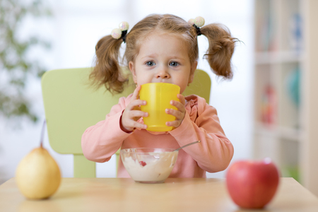 Cute child girl holding glass of water at home