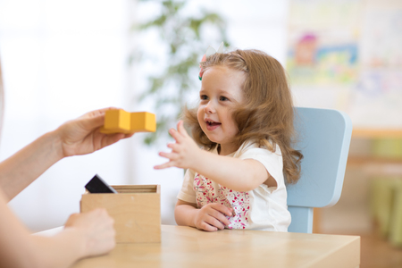 Smart child girl with didactic toys in preschool or daycare Stock Photo