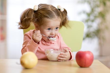 Child girl eating yogurt or fresh cheese with fruits.