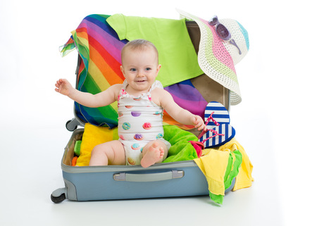 Baby toddler girl sitting in trunk with things for vacation travel Stock Photo