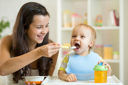 Mother feeding her baby son with spoon. Mother giving healthy food to her adorable child at home Stockfoto