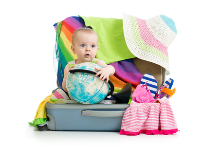 happy baby girl tourist sitting into suitcase with things for travel, vacation