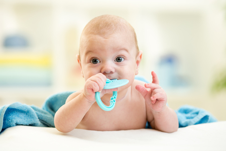 Cute baby infant with teether toy after bathing