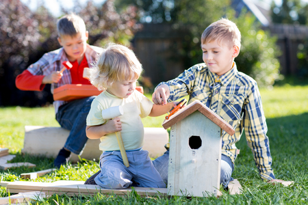 Brothers making wooden birdhouse by hands. Kid teenager teaches his younger brother.