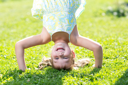 Happy little girl standing on her head on green lawn. Banque d'images
