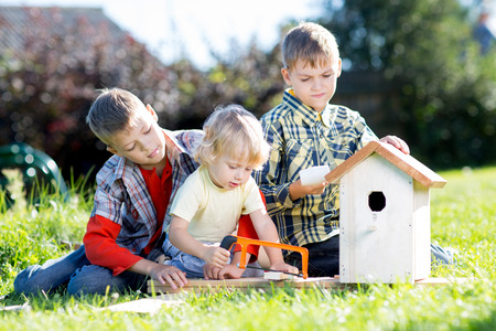 Kids making birdhouse together sitting on the grass. Oldest child teaches youngest brother to work with tools Stock Photo