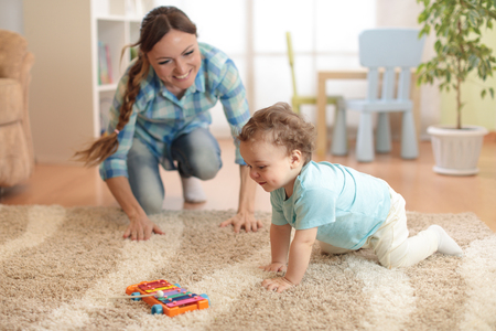 Happy mother looking at her crawling baby son Stock Photo
