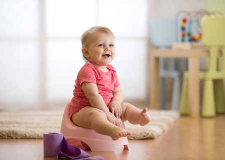 smiling baby sitting on chamber pot with toilet paper roll Reklamní fotografie