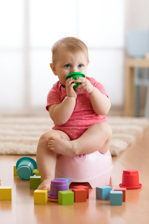 baby sits on a childrens pot, toilet, playing with toys