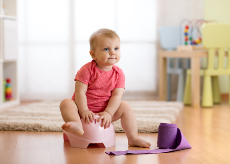Cute baby sitting on chamber pot with toilet paper roll Stock Photo