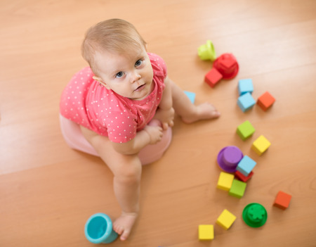 Child sits on chamber pot, toilet, playing with toys. Top view.