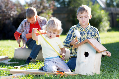 Three kids boys brothers making wooden birdhouse by hands