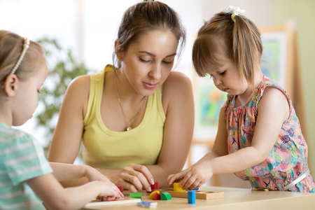 Children starring teacher play with educational toys, stack and arrange colorful pieces. Learning through experience concept, gross and fine motor skills. Banque d'images