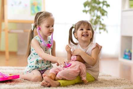 Two kids girls playing doctor with a doll