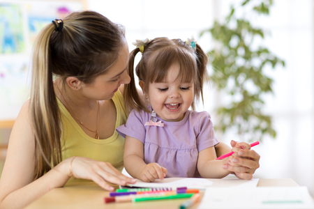 family, children and education concept - mother and daughter drawing