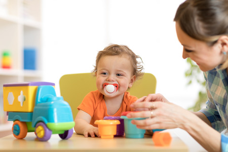Baby and woman playing with puzzle toy in daycare or kindergarten Stock Photo