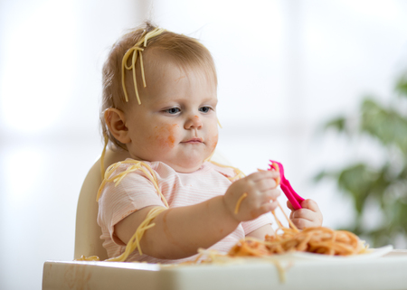 Cute funny baby girl eating spaghetti at home