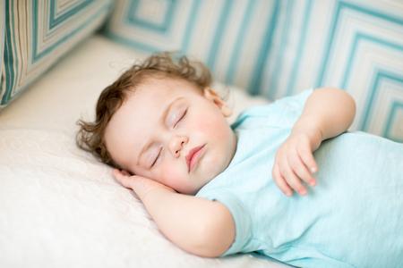 Adorable toddler boy taking a nap