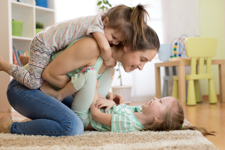 Cheerful kids having fun with mother on floor
