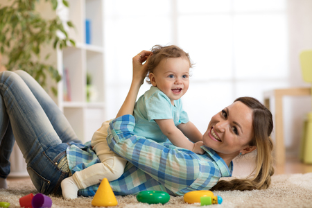 Happy mother and son lying on the floor and playing indoor