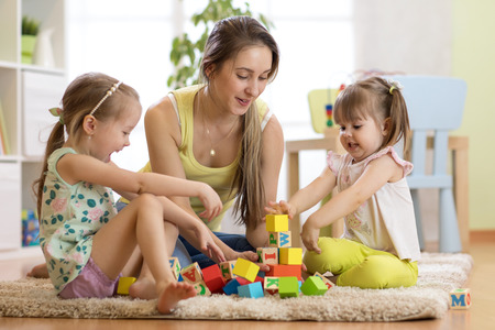 Family activities in the children room. Mother and her kids sitting on the foor playing Stock Photo