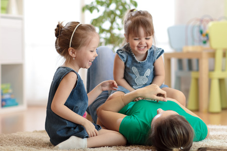 Smiling kids and mom having a fun pastime on floor in children room at home