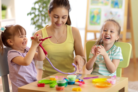 Cheerful children and woman make by hands playing with color dough