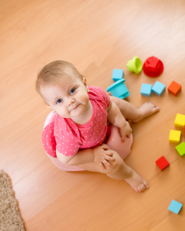 Baby sitting on chamber pot and playing with toys. Top view. Stock Photo