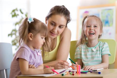 Teacher sitting at desk with two preschooler kids